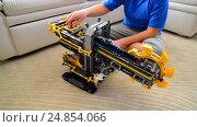 Купить «Kid plays with toy excavator from constructor», видеоролик № 24854066, снято 8 января 2017 г. (c) Володина Ольга / Фотобанк Лори