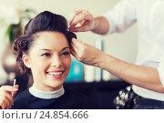 Купить «happy woman with stylist making hairdo at salon», фото № 24854666, снято 15 февраля 2015 г. (c) Syda Productions / Фотобанк Лори