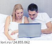 smiling couple in bed with laptop computer, фото № 24855062, снято 23 ноября 2013 г. (c) Syda Productions / Фотобанк Лори