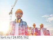Купить «group of smiling builders in hardhats outdoors», фото № 24855162, снято 21 сентября 2014 г. (c) Syda Productions / Фотобанк Лори