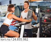 Купить «Woman and man using bicycle gym machinery together», фото № 24855982, снято 4 октября 2016 г. (c) Яков Филимонов / Фотобанк Лори