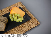 Купить «Gouda cheese and grapes on slate plate», фото № 24856770, снято 16 сентября 2016 г. (c) Wavebreak Media / Фотобанк Лори