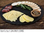 Купить «Slices of cheese, nacho chips and rosemary herbs on plate», фото № 24861046, снято 16 сентября 2016 г. (c) Wavebreak Media / Фотобанк Лори