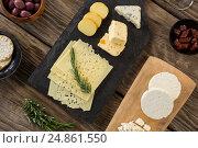 Купить «Variety of cheese, olives, biscuits and rosemary herbs on wooden table», фото № 24861550, снято 16 сентября 2016 г. (c) Wavebreak Media / Фотобанк Лори