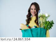 Купить «Beautiful woman carrying grocery bag», фото № 24861934, снято 15 сентября 2016 г. (c) Wavebreak Media / Фотобанк Лори