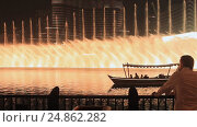 Купить «The Dubai Fountain on October 15, 2014 in Dubai, UAE. The Dubai Fountain is the world's largest choreographed fountain system set on the 30-acre manmade Burj Khalifa Lake», видеоролик № 24862282, снято 15 октября 2014 г. (c) Mikhail Davidovich / Фотобанк Лори