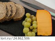 Купить «Brown bread, grapes and gouda cheese on slate board», фото № 24862506, снято 16 сентября 2016 г. (c) Wavebreak Media / Фотобанк Лори