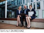 Купить «Businesspeople sitting with laptop in office premises», фото № 24863642, снято 6 июля 2016 г. (c) Wavebreak Media / Фотобанк Лори