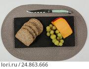 Купить «Brown bread, grapes and gouda cheese with knife on slate board», фото № 24863666, снято 16 сентября 2016 г. (c) Wavebreak Media / Фотобанк Лори