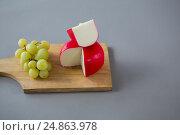 Купить «Gouda cheese with grapes on chopping board», фото № 24863978, снято 16 сентября 2016 г. (c) Wavebreak Media / Фотобанк Лори