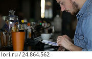 A young man uses tablet while sitting at the bar. Стоковое видео, видеограф Загородний Кирилл / Фотобанк Лори