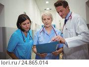 Купить «Team of doctors having discussion over file in corridor», фото № 24865014, снято 9 июля 2016 г. (c) Wavebreak Media / Фотобанк Лори