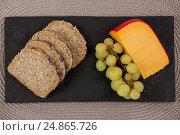 Купить «Slices of brown bread, grapes and gouda cheese on slate board», фото № 24865726, снято 16 сентября 2016 г. (c) Wavebreak Media / Фотобанк Лори