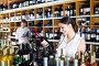 Happy young woman choosing bottle in wine shop, фото № 24866134, снято 15 января 2017 г. (c) Яков Филимонов / Фотобанк Лори