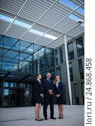 Купить «Confident businesspeople standing in the office premises», фото № 24868458, снято 6 июля 2016 г. (c) Wavebreak Media / Фотобанк Лори