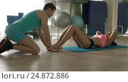 Woman doing sit ups with personal trainer in gym. Стоковое фото, фотограф Станислав Толстнев / Фотобанк Лори