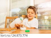 Купить «Little boy pouring milk to glass in the kitchen», фото № 24873774, снято 4 декабря 2016 г. (c) Сергей Новиков / Фотобанк Лори