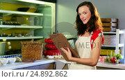 Купить «Female staff making a checklist at counter», видеоролик № 24892862, снято 22 июля 2018 г. (c) Wavebreak Media / Фотобанк Лори