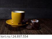 Желтая чашка с блюдцем с конфетами на деревянном фоне. Стоковое фото, фотограф Беляева Юлия / Фотобанк Лори