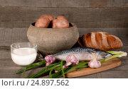 Горшочек с картофелем, чашка с молоком, рыба, хлеб, чеснок и лук на деревянном фоне. Стоковое фото, фотограф Беляева Юлия / Фотобанк Лори