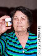 Грустная пожилая женщина задумчиво смотрит на флакон медикаментов, фото № 24909418, снято 6 января 2017 г. (c) Эдуард Паравян / Фотобанк Лори