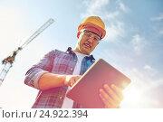 Купить «builder in hardhat with tablet pc at construction», фото № 24922394, снято 21 сентября 2014 г. (c) Syda Productions / Фотобанк Лори