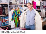 Купить «Young female customer examining new bathrobe», фото № 24958902, снято 13 ноября 2019 г. (c) Яков Филимонов / Фотобанк Лори