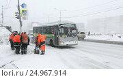 Купить «Рабочие коммунальных служб чистят тротуар от снега и льда во время снегопада», видеоролик № 24967914, снято 12 января 2017 г. (c) А. А. Пирагис / Фотобанк Лори