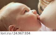 Купить «Baby feeds on MOM's breasts. Mother has blond hair.», видеоролик № 24967934, снято 20 января 2017 г. (c) Mikhail Davidovich / Фотобанк Лори