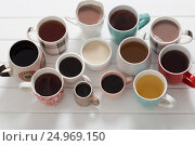 Купить «Many cups of hot drinks on white wooden table», фото № 24969150, снято 24 января 2017 г. (c) Майя Крученкова / Фотобанк Лори