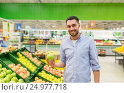 Купить «happy man buying green apples at grocery store», фото № 24977718, снято 21 октября 2016 г. (c) Syda Productions / Фотобанк Лори