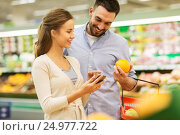 Купить «couple with smartphone buying oranges at grocery», фото № 24977722, снято 21 октября 2016 г. (c) Syda Productions / Фотобанк Лори