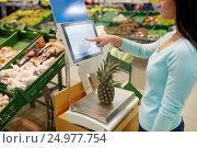 Купить «woman weighing pineapple on scale at grocery store», фото № 24977754, снято 2 ноября 2016 г. (c) Syda Productions / Фотобанк Лори