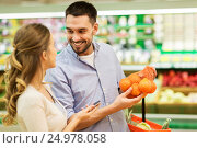 Купить «happy couple buying oranges at grocery store», фото № 24978058, снято 21 октября 2016 г. (c) Syda Productions / Фотобанк Лори