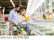 Купить «couple with shopping cart buying food at grocery», фото № 24978082, снято 21 октября 2016 г. (c) Syda Productions / Фотобанк Лори