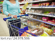 Купить «woman with food in shopping cart at supermarket», фото № 24978506, снято 2 ноября 2016 г. (c) Syda Productions / Фотобанк Лори