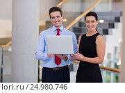 Купить «Happy business executives holding a laptop», фото № 24980746, снято 3 ноября 2016 г. (c) Wavebreak Media / Фотобанк Лори