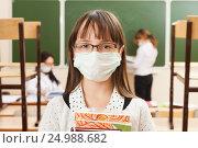 Купить «Школьница в медицинской противовирусной маске», фото № 24988682, снято 20 октября 2014 г. (c) Владимир Мельников / Фотобанк Лори