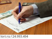 Купить «Мужчина заполняет налоговую декларацию», фото № 24993494, снято 29 января 2017 г. (c) Акиньшин Владимир / Фотобанк Лори