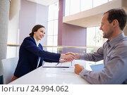 Купить «Businesswoman shaking hands with colleague at desk», фото № 24994062, снято 3 ноября 2016 г. (c) Wavebreak Media / Фотобанк Лори