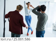 Купить «Female model posing for photographer», фото № 25001586, снято 1 сентября 2016 г. (c) Wavebreak Media / Фотобанк Лори