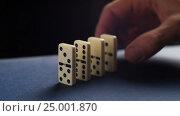 Купить «Closeup of a hand putting a domino. Dominoes falling. Nervous and failure.», видеоролик № 25001870, снято 30 января 2017 г. (c) Сергей Кальсин / Фотобанк Лори