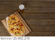 Купить «Delicious pizza served on pizza tray with a glass of beer on wooden plank», фото № 25002210, снято 30 сентября 2016 г. (c) Wavebreak Media / Фотобанк Лори