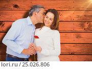Composite image of husband kissing wife while holding rose. Стоковое фото, агентство Wavebreak Media / Фотобанк Лори
