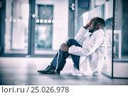 Купить «Worried doctor sitting floor», фото № 25026978, снято 25 июня 2019 г. (c) Wavebreak Media / Фотобанк Лори