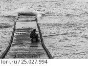 Одинокий рыбак на волнорезе в дождливую погоду. Стоковое фото, фотограф oleg didenko / Фотобанк Лори
