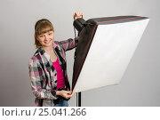 Фотограф в студии устанавливает правильное направление света софтбокса. Стоковое фото, фотограф Иванов Алексей / Фотобанк Лори