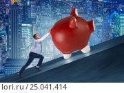 Купить «Man pushing piggybank uphill in business concept», фото № 25041414, снято 17 февраля 2019 г. (c) Elnur / Фотобанк Лори
