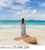 Woman enjoying Anse Patates picture perfect beach on La Digue Island, Seychelles. Стоковое фото, фотограф Matej Kastelic / Фотобанк Лори
