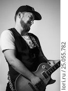Купить «Handsome bearded musician playing guitar over gray background», фото № 25055782, снято 17 ноября 2016 г. (c) Marina Goncharova / Фотобанк Лори